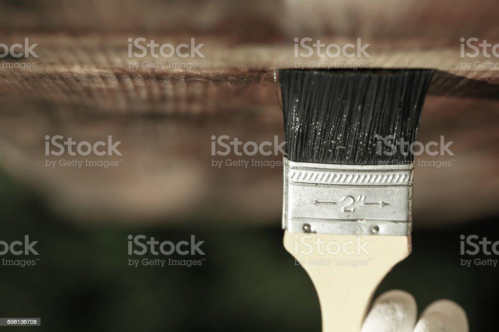 Paintbrush sliding over wooden ceiling surface stock photo