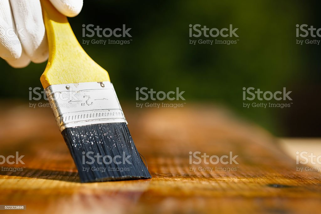 Paintbrush sliding over wooden surface, protecting wood stock photo