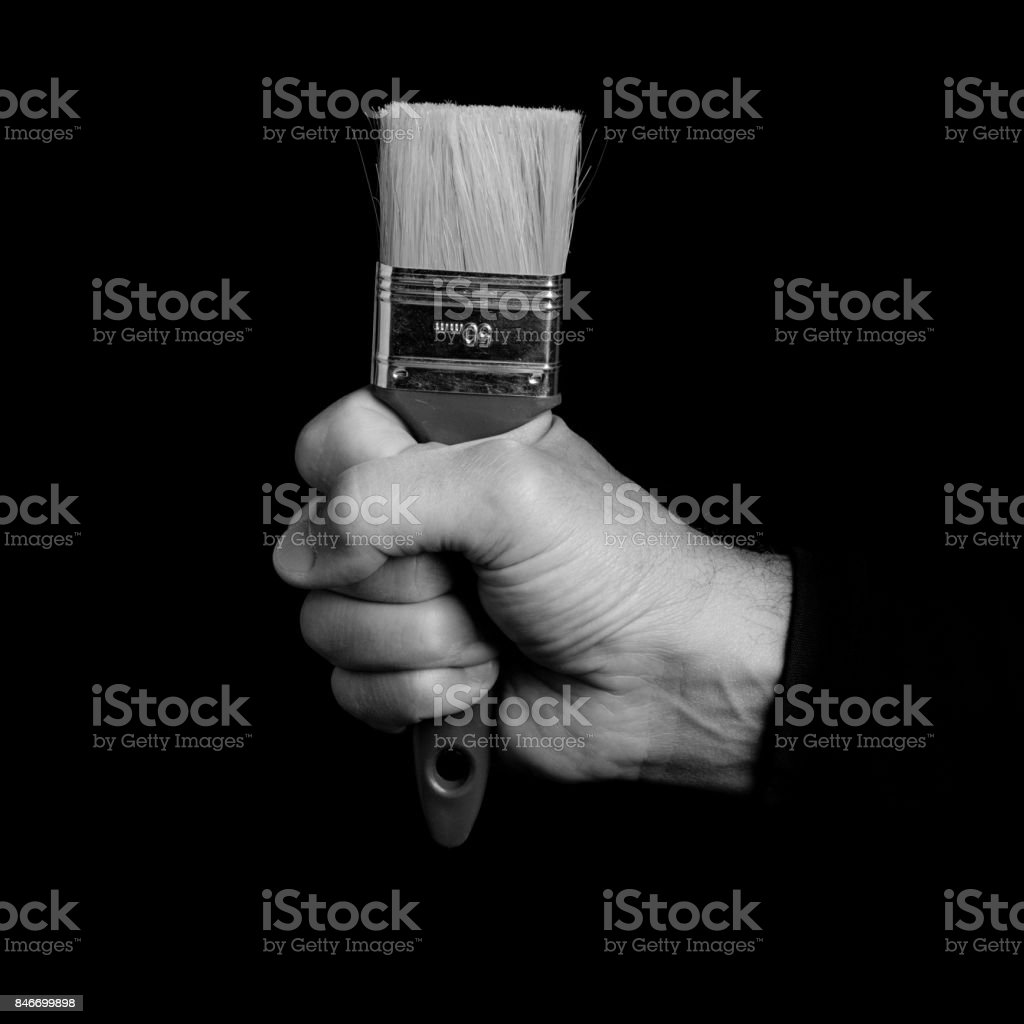 paintbrush - tools in a man's hand - black and white photo stock photo