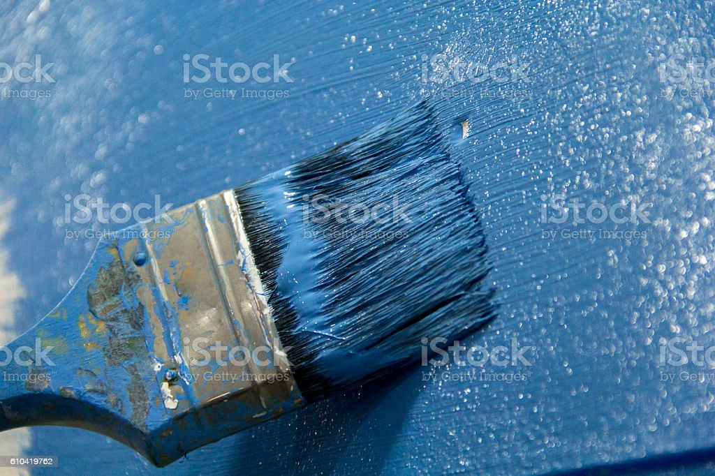 Paintbrush with blue paint, painting on wall stock photo