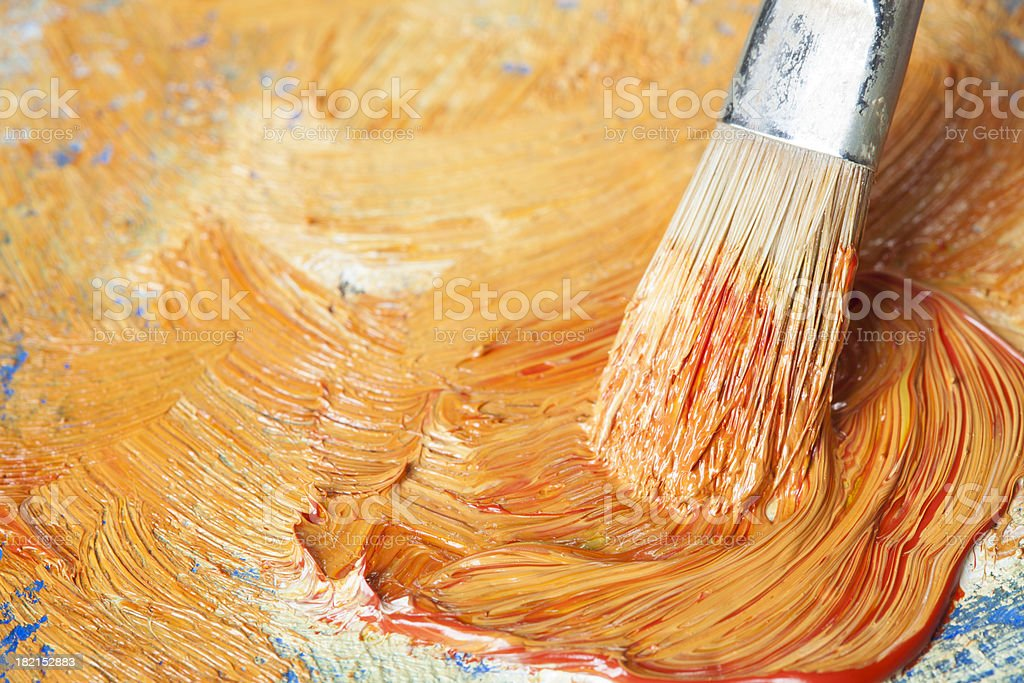 Paintbrush with orange oil paint on a classical palette royalty-free stock photo