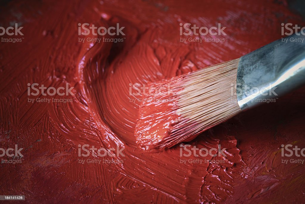 Paintbrush with red oil paint on a classical palette royalty-free stock photo