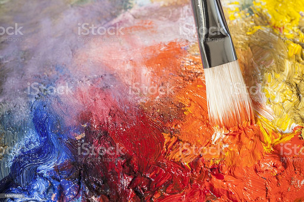 Paintbrush with red oil paint on a classical palette stock photo