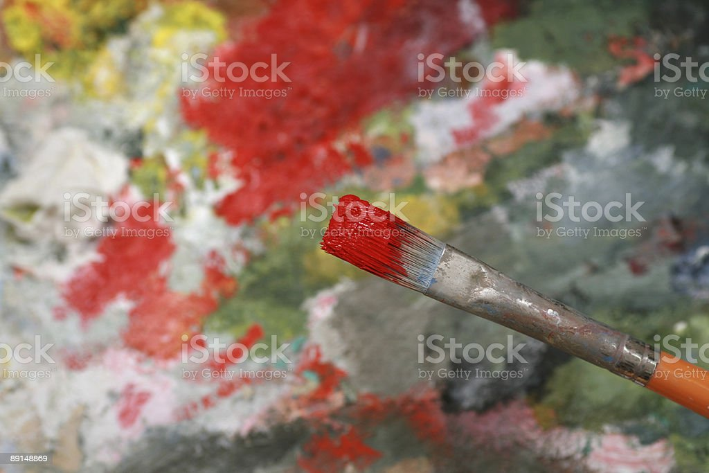 Paintbrush with red oil paints and a palette royalty-free stock photo