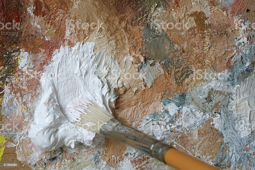 Paintbrush with white oil color on a classical palette royalty-free stock photo