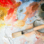 Paintbrush with white oil paint on a classical palette