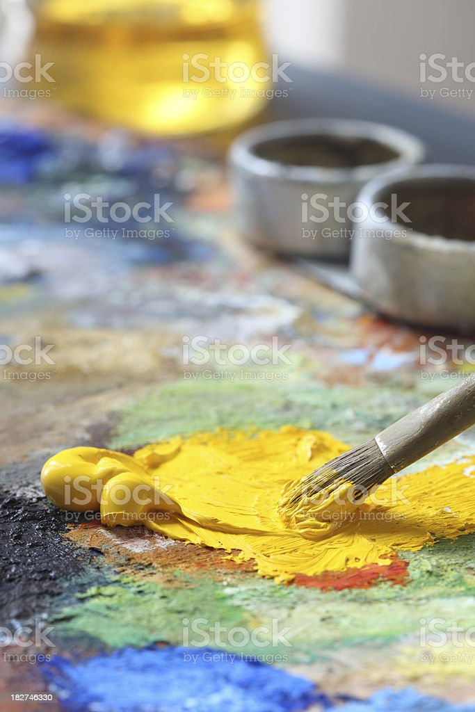 Paintbrush with yellow oil paint on a classical palette royalty-free stock photo