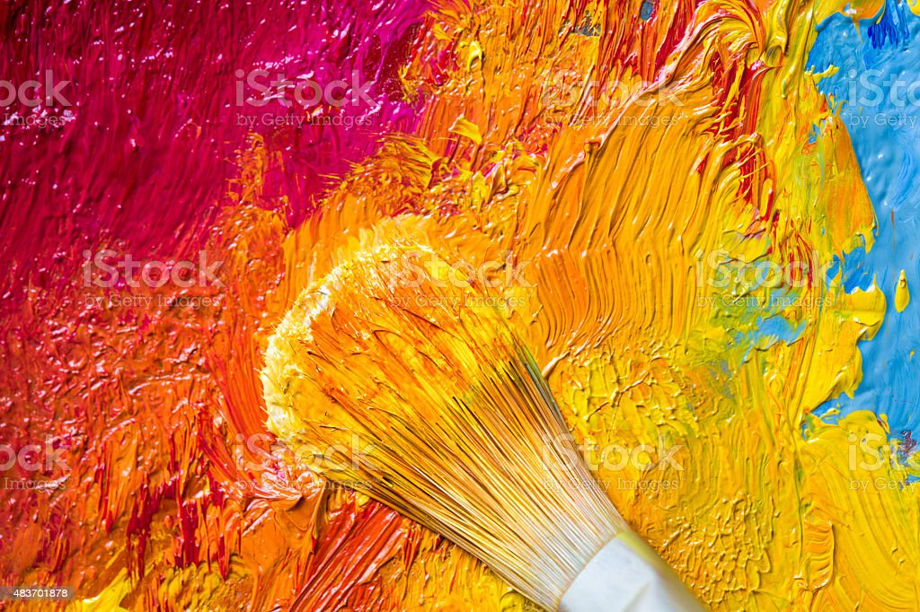 Paintbrush with yellow oil paint on a classical palette stock photo