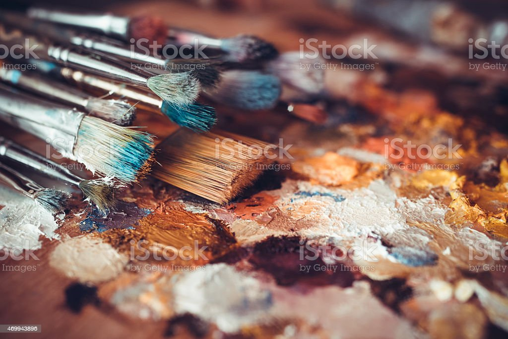 Paintbrushes closeup, artist palette and multicolor paint stains stock photo