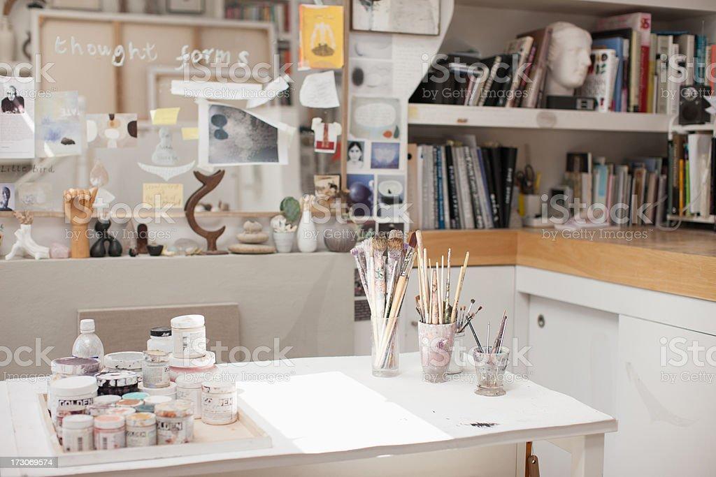 Paintbrushes in jars in art studio stock photo