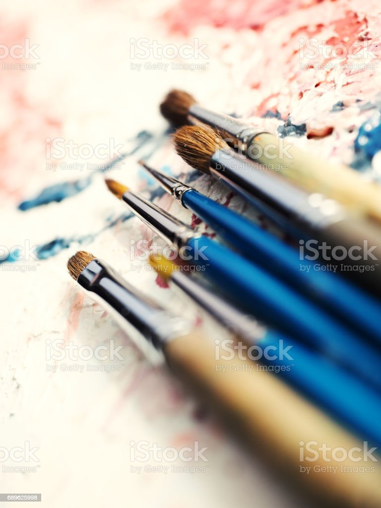 Paintbrushes on oil painting canvas. Shallow depth of field. stock photo