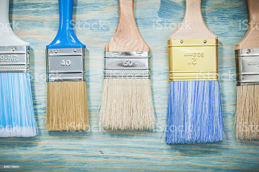 Paintbrushes on wooden board top view construction concept stock photo