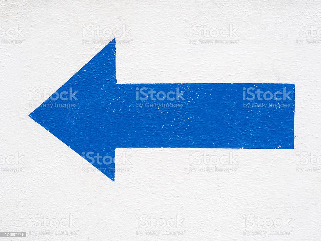 Painted blue arrow on white concrete wall stock photo