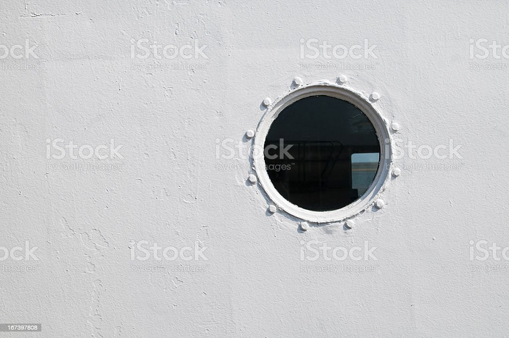 Painted brass porthole on the side of a ship stock photo