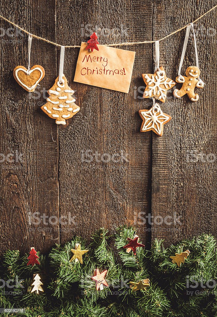 painted by gingerbread cookie hanging on spruce branches against stock photo