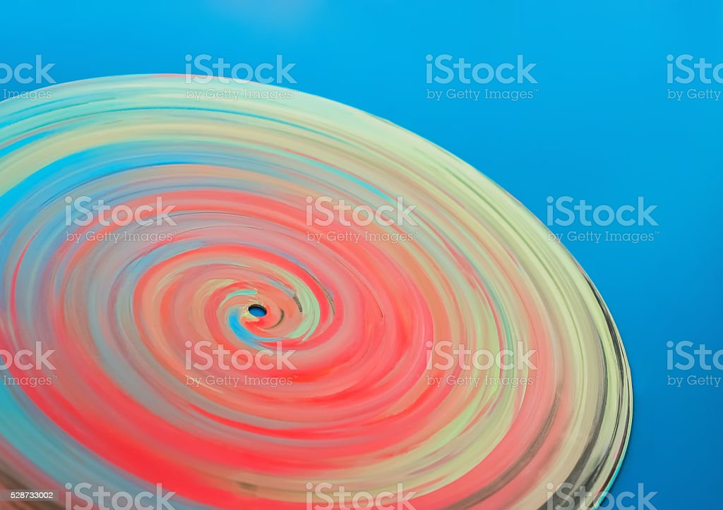 Painted colorful disc on a blue background stock photo