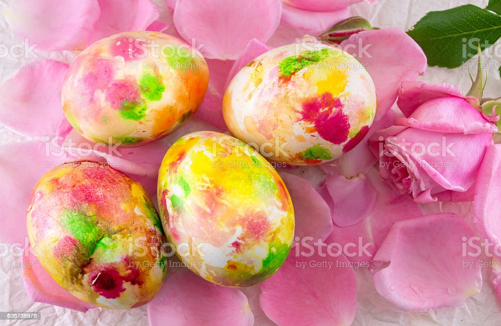 Painted Easter egg on pink rose petals stock photo