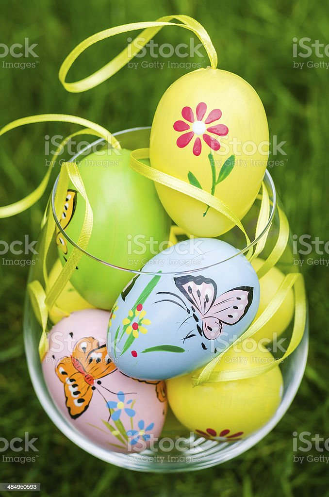 Painted easter eggs in glass on green grass royalty-free stock photo