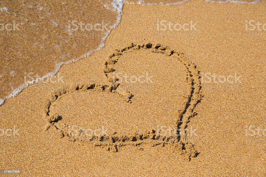 Painted heart in the sand on the beach stock photo