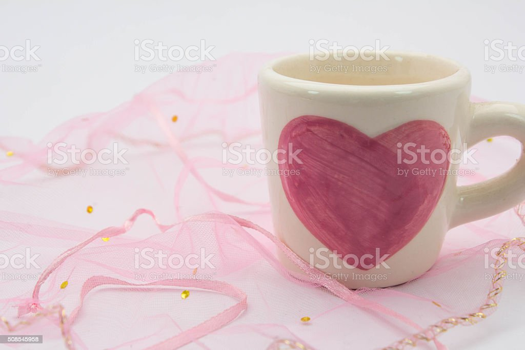 Painted heart-shaped cups placed on the fabric stock photo