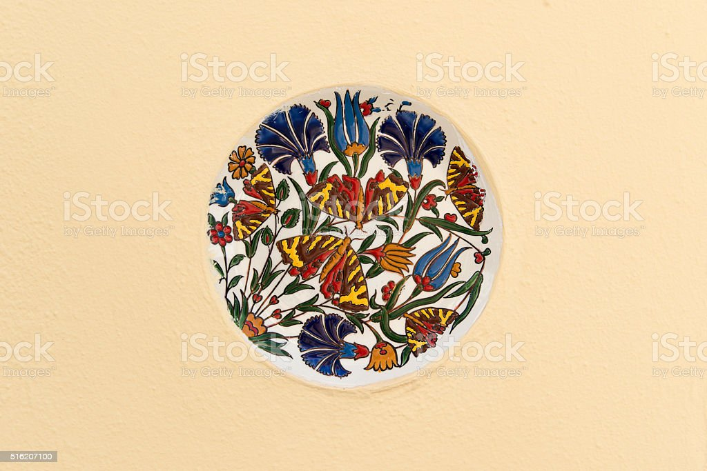 Painted plate isolated on wall stock photo