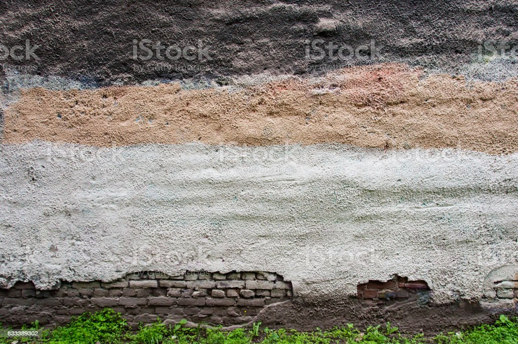 painted striped wall above green grass stock photo