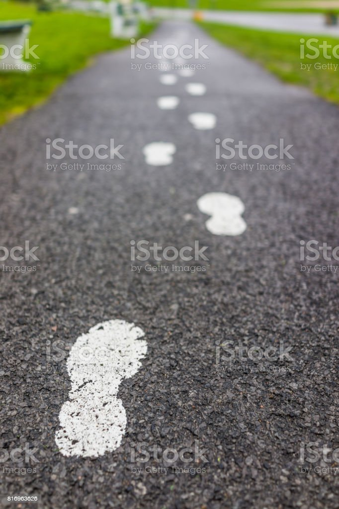 Painted white footprints on asphalt road path as guide stock photo
