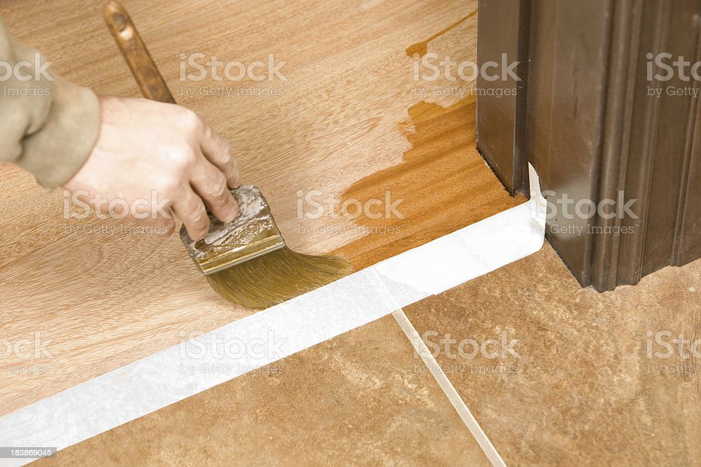 Painter Brushing Clear Polyurethane on Hardwood Floor stock photo
