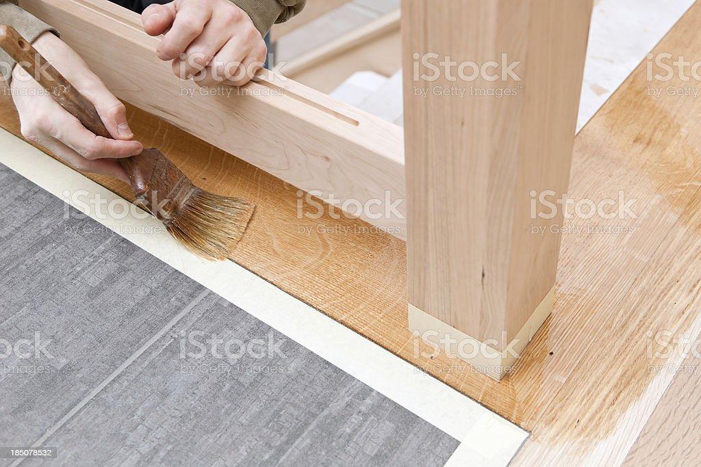 Painter Brushing Clear Polyurethane on Hardwood Floor stock photo