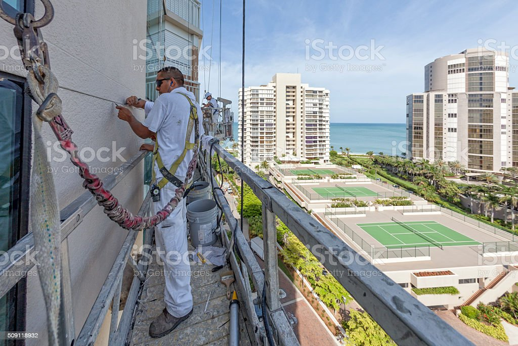 Painter Clearing the Cracks on a Highrise Building Being Prepped stock photo