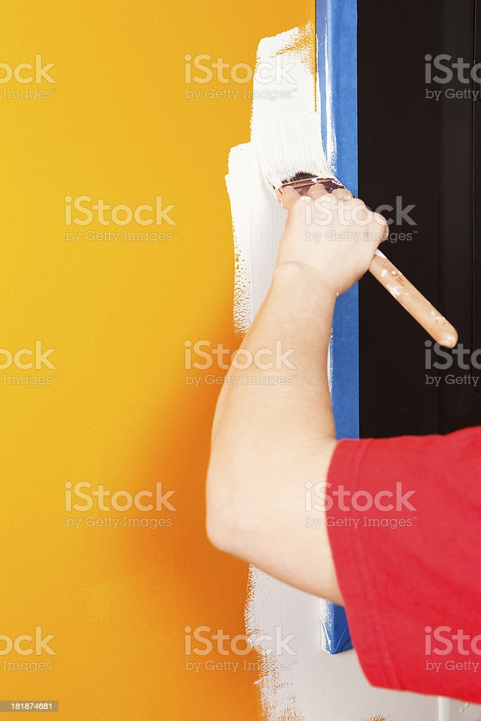 Painter Cutting In White Paint next to Blue Tape stock photo