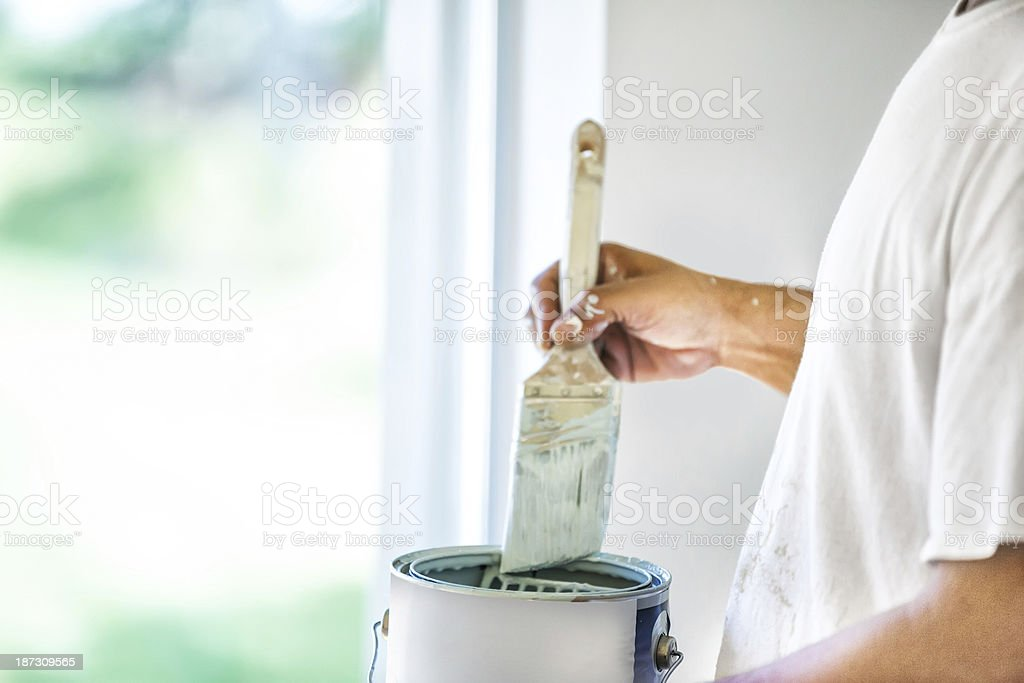 Painter dipping his brush in paint can stock photo