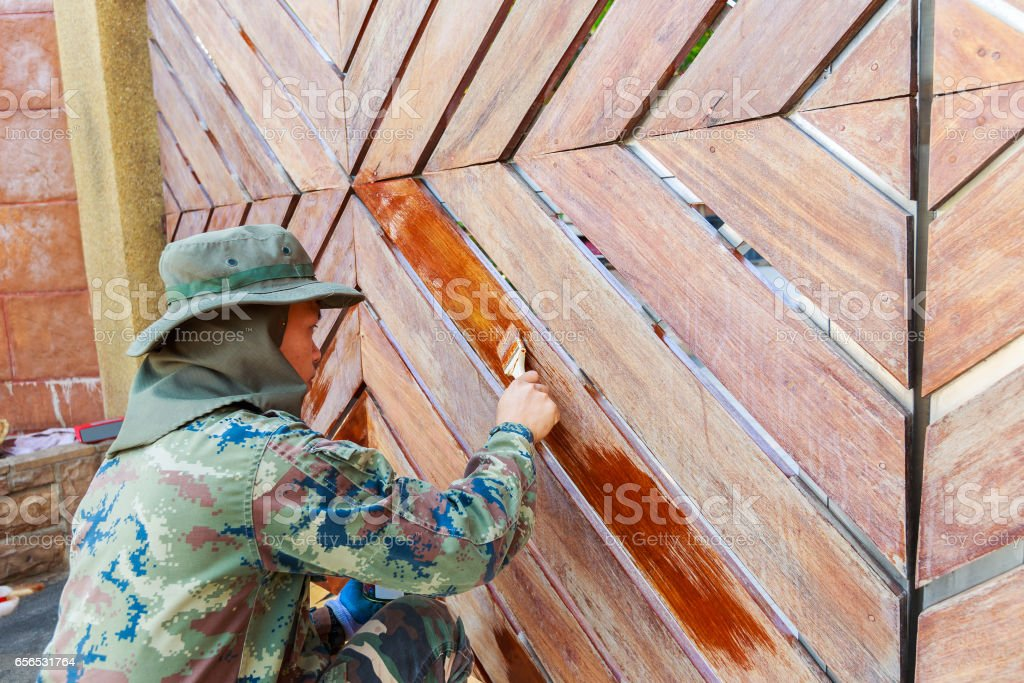 Painter man at work, painting a wooden door with brush, home improvement and renovation. stock photo