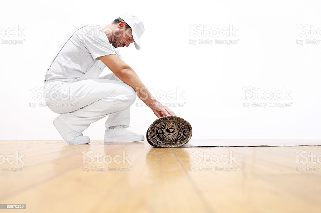 painter man at work, rolls the cardboard on the floor stock photo