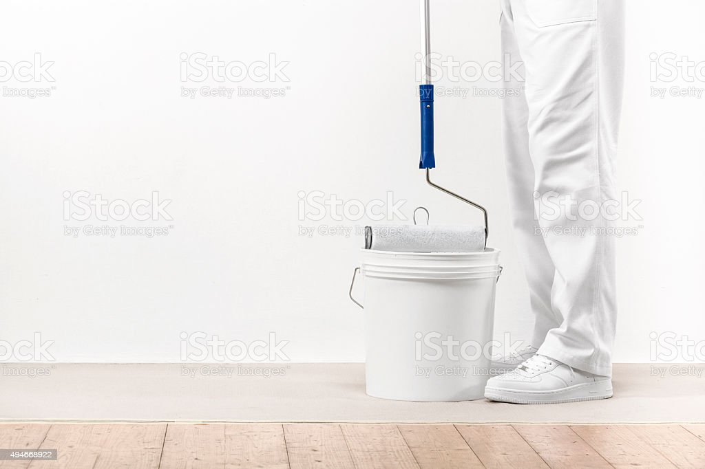 Painter man takes the color with paintroller from the bucket stock photo