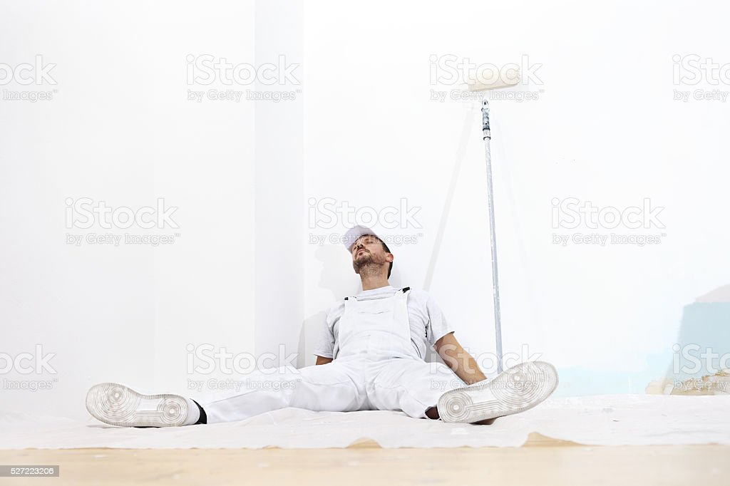painter man tired, lying on the floor stock photo