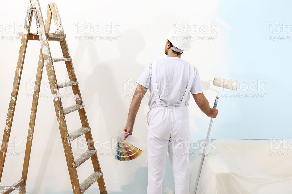 painter man with a paint roller and color samples stock photo