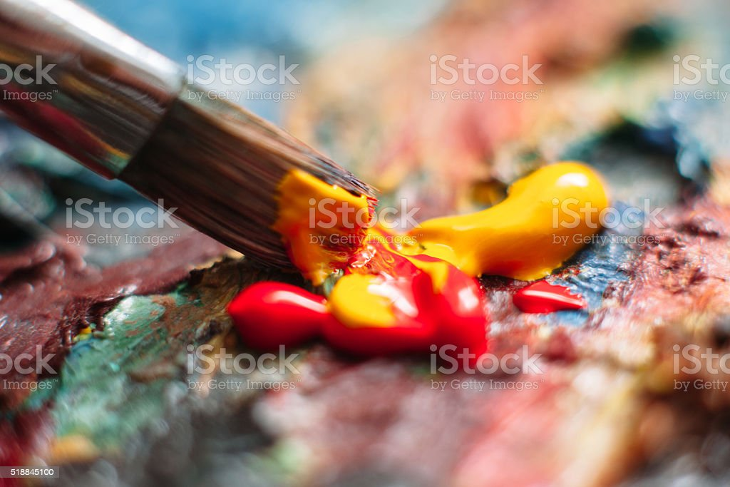 Painter mixes paint on the palette. Closeup stock photo