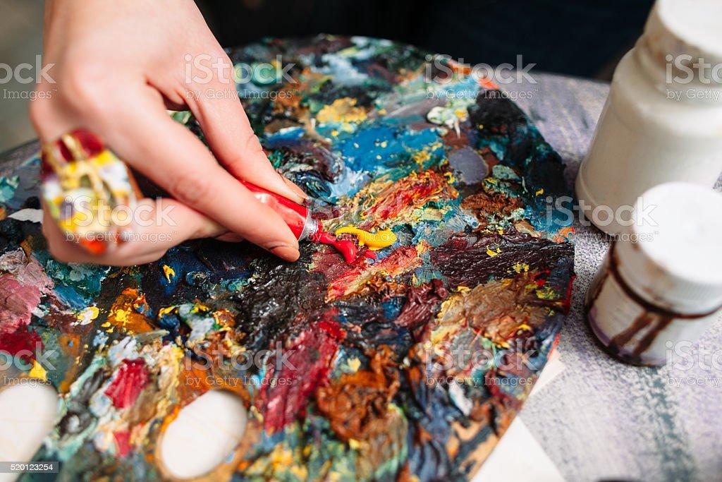 Painter mixes paint on the palette. Closeup stock photo
