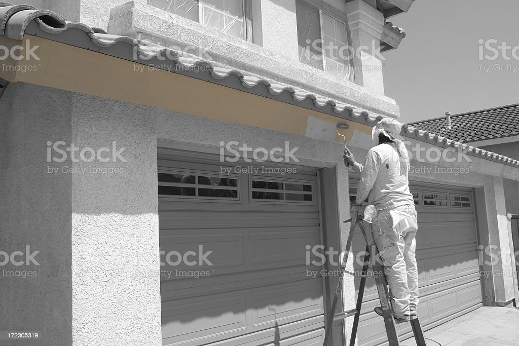 Painter on a stool painting the building from white to beige royalty-free stock photo
