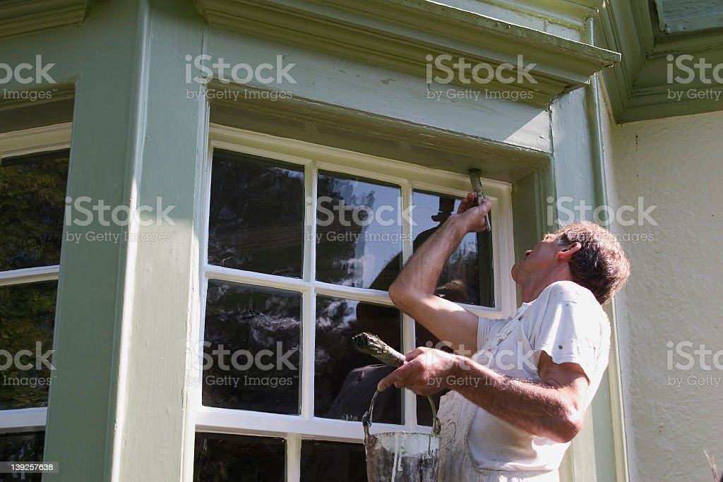 Painter painting the exterior of a house with trimming brush royalty-free stock photo