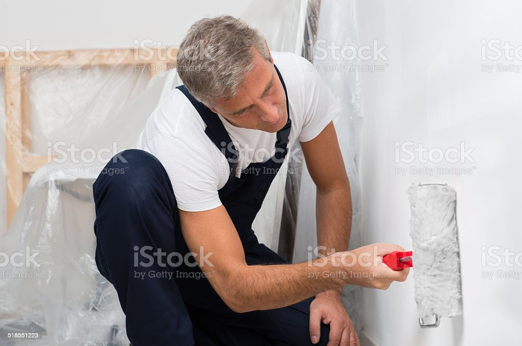 Painter Painting Wall With Roller stock photo