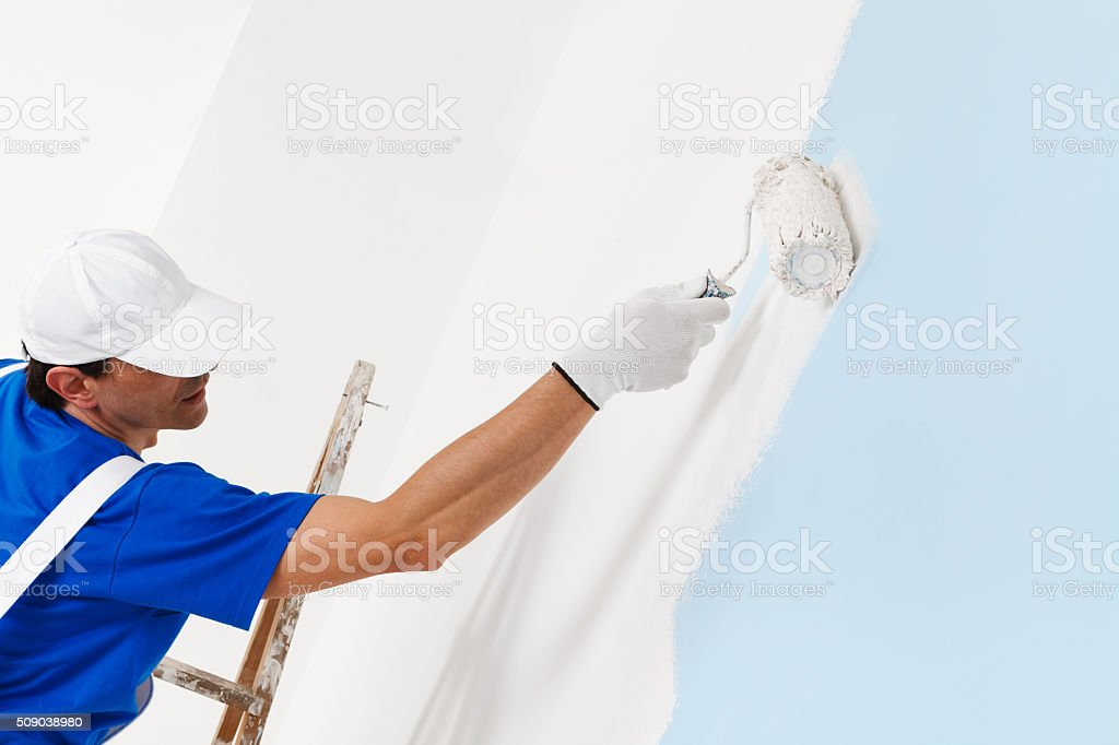 painter painting with paint roller stock photo