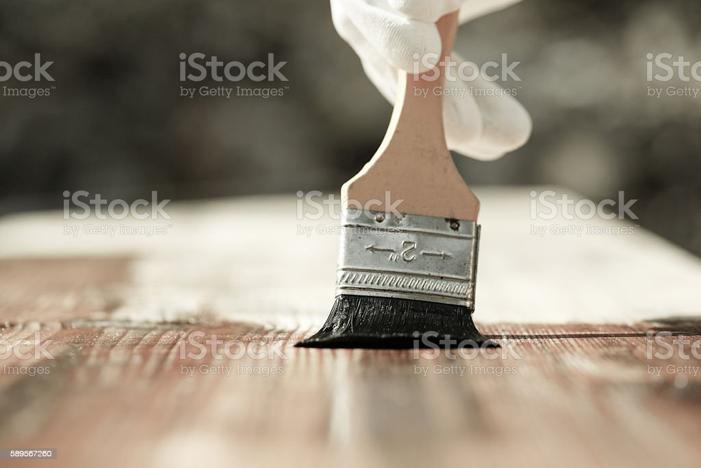 Painter painting wooden surface, protecting wood stock photo