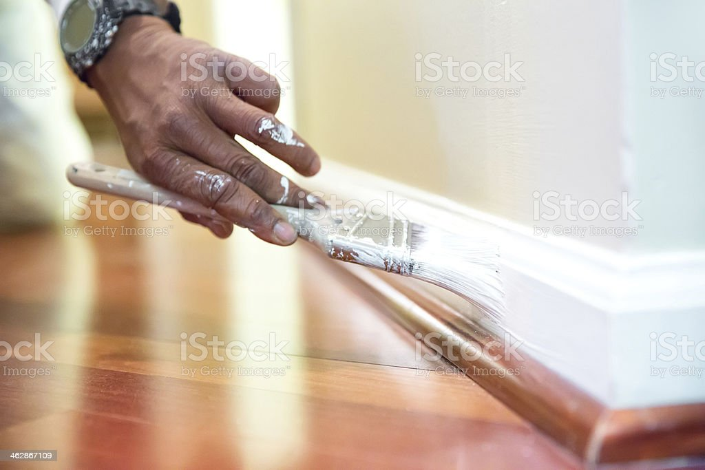 Painter paints baseboard in a home stock photo