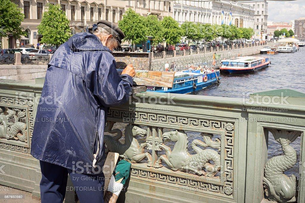 painter paints on Nevskom prospectus the boats in Fontanka river stock photo