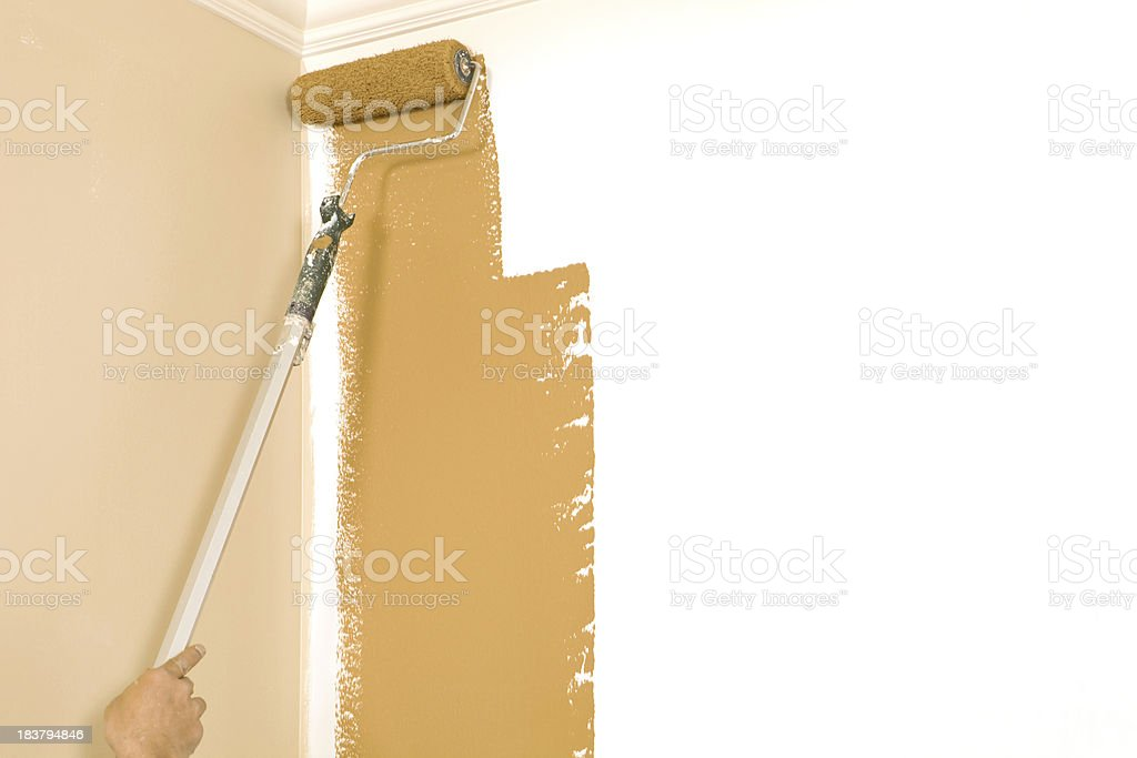 Painter Rolling Brown Paint on Primed Wall Corner stock photo