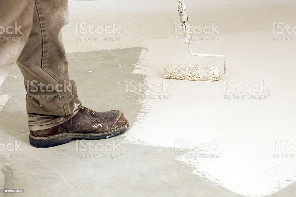 Painter Rolling Epoxy Paint on Concrete Floor royalty-free stock photo