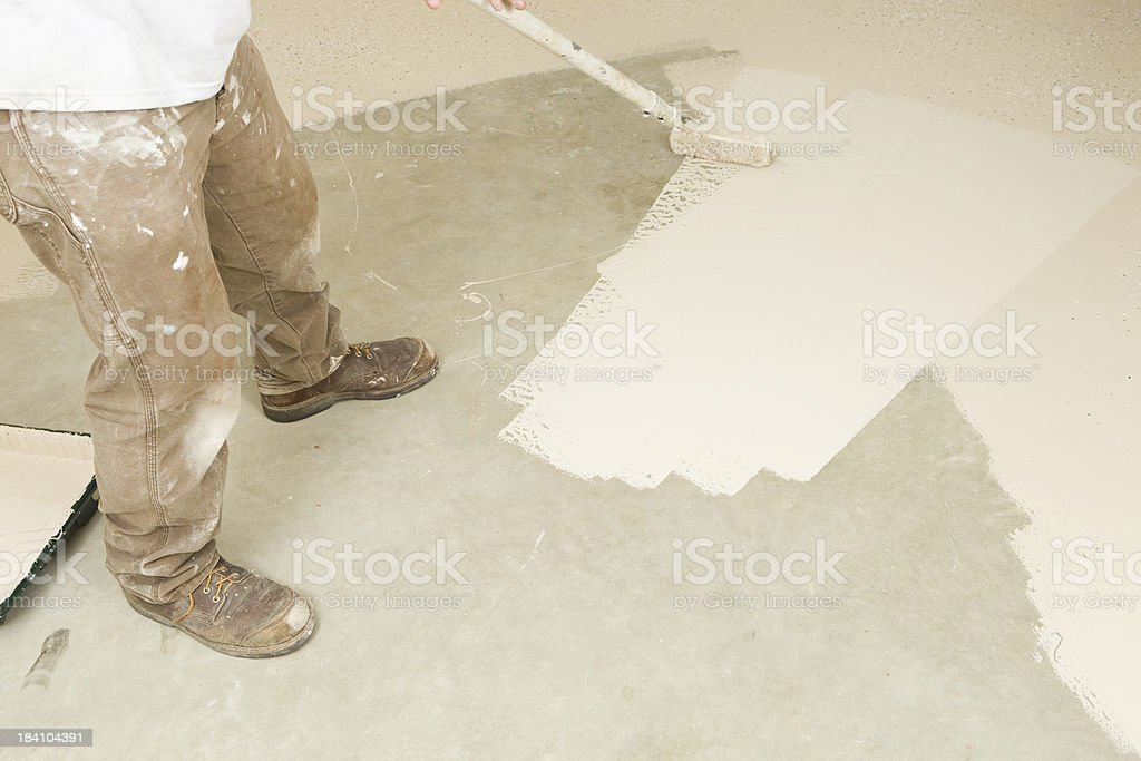 Painter Rolling Epoxy Paint on Concrete Floor royalty-free stock photo