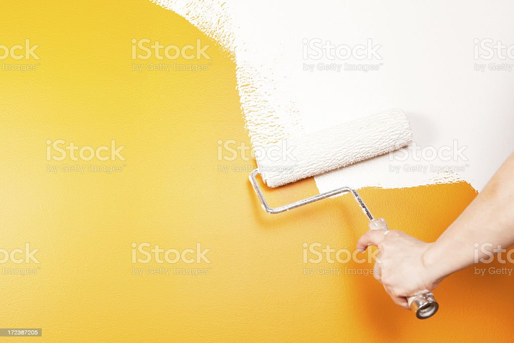 Painter Rolling White Paint over Old Orange Wall stock photo